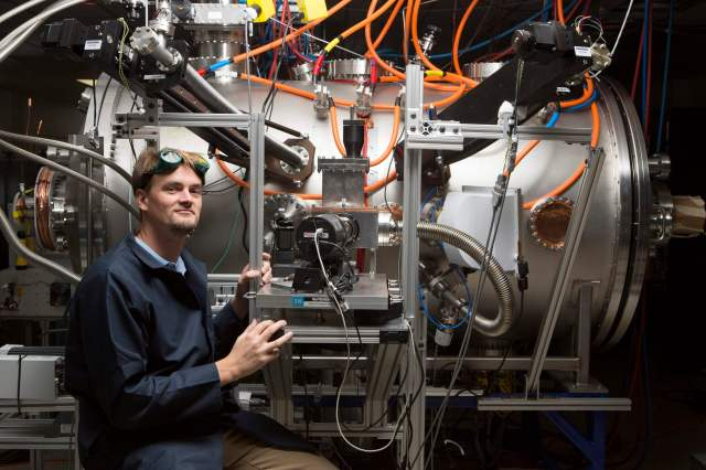 Tom McGuire stands next to the compact fusion reactor experiment inside his lab at the Skunk Works in Palmdale